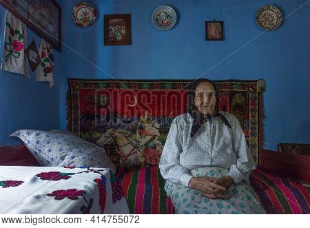 Salaj, Transylvania, Romania-may 14, 2018: Very Old Woman Sitting Alone Inside Her Little Charming H
