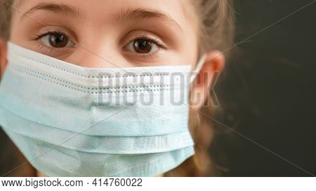 Kid Face In Medical Mask. Covid Coronavirus Pandemic Medicine Concept. Portrait Of A Face Girl Kid C
