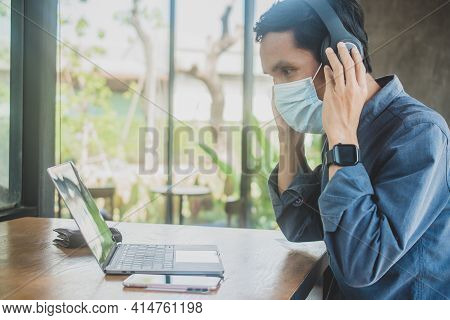 Man Wear Facemask Working Laptop  In Cafe , People Using Phone , Asian Man Use Headphone Listening M