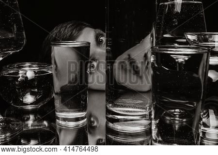 Black And White Surreal Portrait Of A Man Looking Through Glasses Of Water