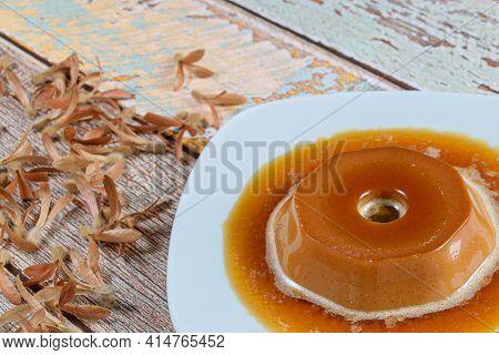 Closeup Of Dulce De Leche Pudding With Caramel Syrup, Alongside Flying Seeds (triplaris Americana).