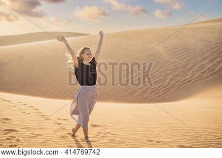 Young Beautiful Woman Traveling In The Desert. Sandy Dunes And Blue Sky On Sunny Summer Day. Travel,