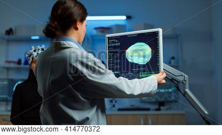 Neurologist Doctor Looking At Monitor Examining Brain Scan