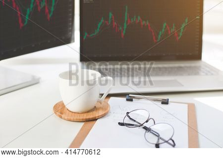 Laptop And Monitor With Exchange Charts. Trading Discussion And Analysis Of Stock Market Trading Cha