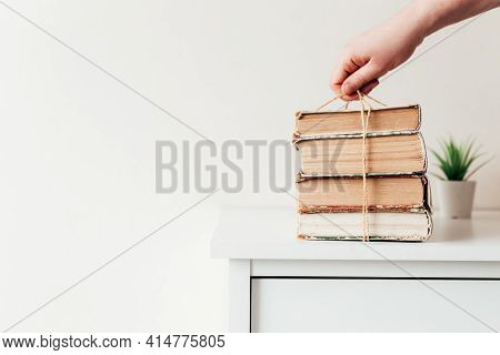 Hand Holding A Stack Of Old Books In The Library, Concept Of Learning, Study And Education, Concept