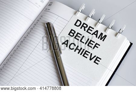 Text Dream Belief Achieve On The Short Note Texture Background With Pen. Business