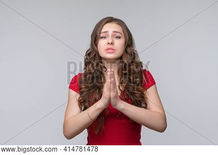 Attractive Brunette Girl Looks With Imploring Expression Asks To Give One More Chance, Keeps Palms P