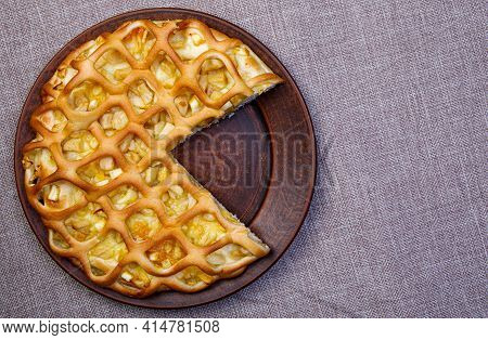 Apple Pie With A Cut Piece On A Ceramic Plate. Top View. Linen Tablecloth.