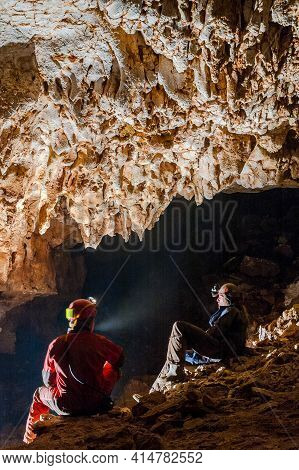 Speleologists Wondering And Admiring Stalactites In A Cave