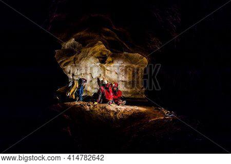 Speleologists Exploring A Deep Cave
