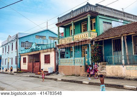Baracoa, Cuba - October 25, 2019: Cuban Children Playing On The Street With Colorful Traditional Hou