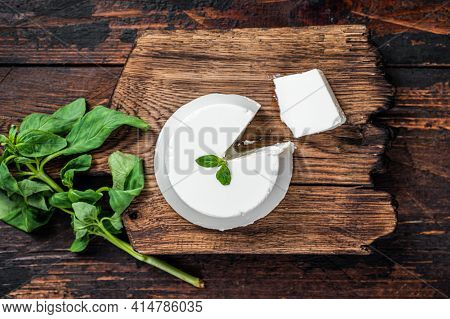 Fresh Ricotta Cream Cheese On Wooden Board With Basil. Dark Wooden Background. Top View