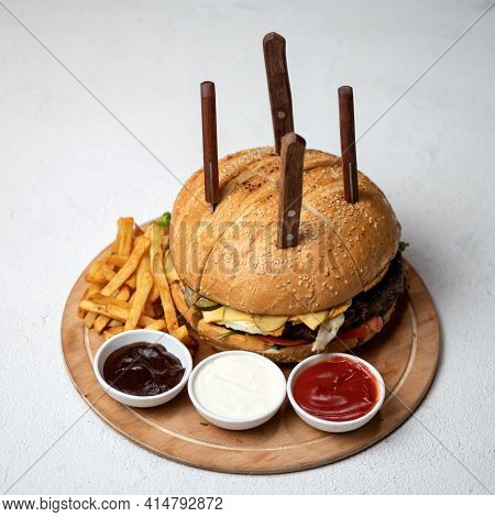 Huge Size Hamburger Cut Into Four Quarters With Knives Stuck In. Fast Food Nutritious Lunch From Big