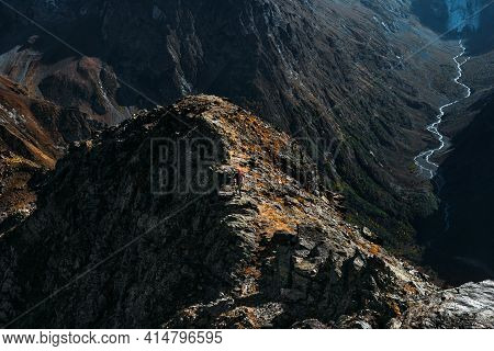 Traveler In The Mountains. A Man Runs Along A Mountain Range In Dombay. Man At Sunrise In The Mounta