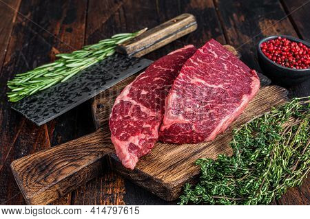 Raw Denver Cut Black Angus Beef Steak On A Butcher Board With Meat Cleaver. Dark Wooden Background.