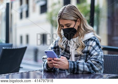 Young Woman With The Mask Against Covid-19 With The Smartphone Sitting On The Terrace Of A Cafeteria