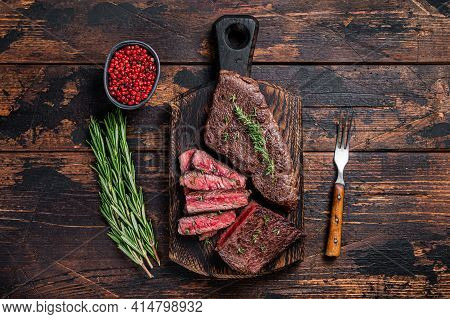 Grilled Sliced Skirt Beef Meat Steak On A Cutting Board With Herbs. Dark Wooden Background. Top View