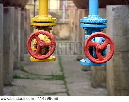 Two Drain Valves Blue And Yellow With Red Hand Wheels Over Concrete Elements And Brown Tanks Backgro