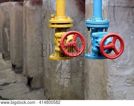 Two Drain Valves Yellow And Blue With Red Hand Wheels Over Concrete Elements And Brown Tanks Backgro