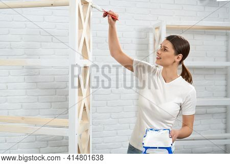 Close Up Of Smiling Beautiful Woman Painting In White Color Rack In Bright Room. Concept Of Improvem
