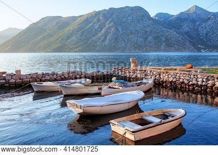 White Wooden Boats For Fishing On The Harbour . Morning Outlook Of Mountains And Lagoon