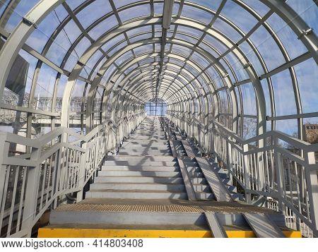 Pedestrian Crosswalk Under A Glass Roof. Stairs Of The Covered Aboveground Pedestrian Bridge