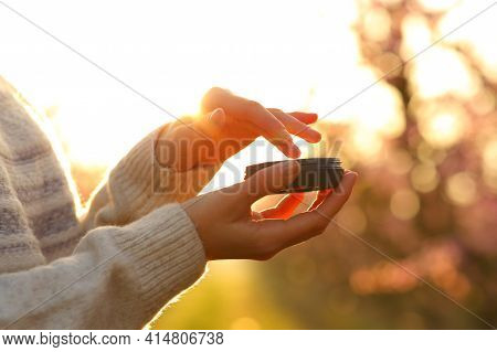 Close Up Of A Woman Hands Applying Moisturizer Cream At Sunset In A Filed In Spring
