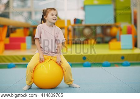 Kids Doing Exercises With Big Ball In Gym At Kindergarten Or Elementary School. Children Sport And F