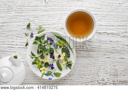 Tea Cup Of Fresh Herbal Leaves On White Wooden Background, Top View, Place For Text. Healthy Concept