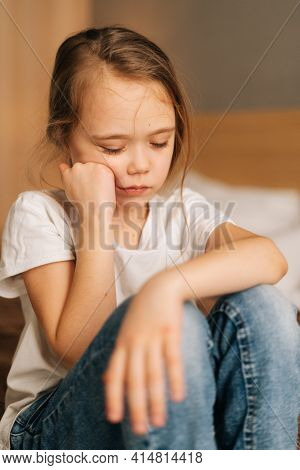 Close-up Face Of Distraught Beautiful Little Girl With Wet Eyes From Tears Sits On Bed In Bedroom An
