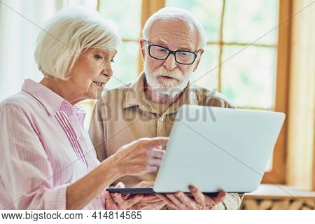 Elderly Couple Using Computer Near The Window At Their House