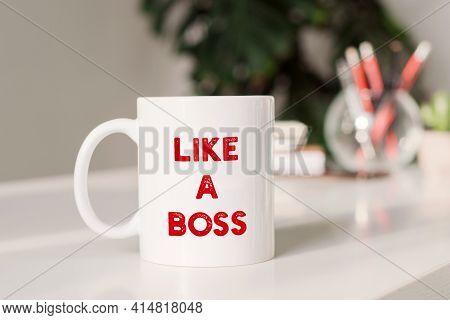 Coffee Mug With Text Like A Boss In Workplace Background.
