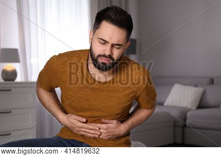 Young Man Suffering From Stomach Ache At Home. Food Poisoning