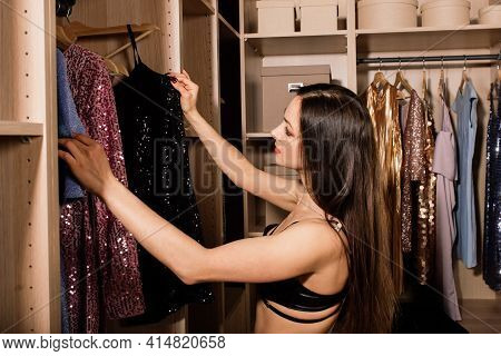 Young Woman In Underwear Thinking What Dress To Wear In Front Of The Clothes In Wardrobe. Nothing To