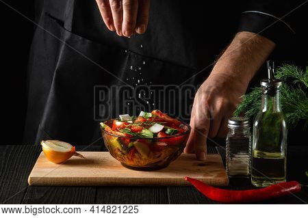 Chef Sprinkles Salted Fresh Vegetable Salad In A Plate On A Wooden Table. Cooking Healthy Food In Th
