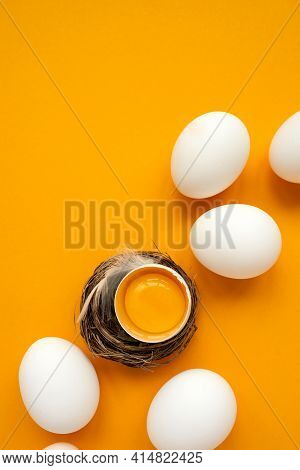 White Eggs And Egg Yolk Into Nest On Yellow Background. Top View. Flat Lay. Easter Celebration