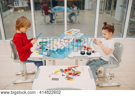 Smiling Kids Boy And Girl Child Constructor Checking Technical Toy. Children Robotics Constructor As