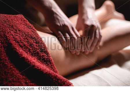 Close-up Masseur Man Doing Thigh Massage Of The Leg To A Woman Athlete Client In A Dark Room Of A Ma