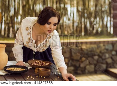 Sexy Caucasian Female In Rural Decorated Dress Posing With Wooden Plates Filled With Frigole Beans