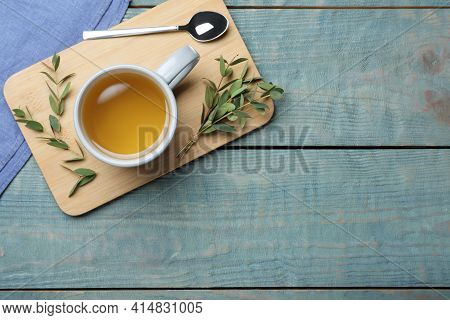 Cup Of Aromatic Eucalyptus Tea On Light Blue Wooden Table, Top View. Space For Text
