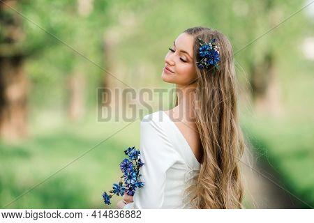 A Young Happy Girl With Long Hair In A White Dress With Cornflowers Enjoys The Summer Nature. Portra