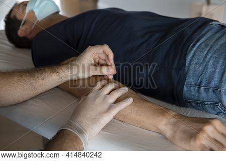 Close Up Of Physiotherapist Hands With Surgical Gloves Introducing A Needle To A Male Patient's Arm