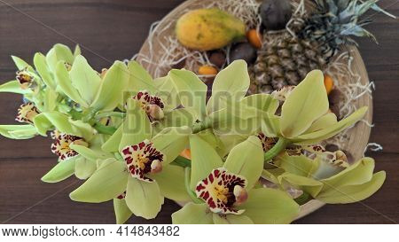 Close-up Of A Green And Yellow Rare Orchid. Selective Focus. Exotic Fruits On A Blurred Background.