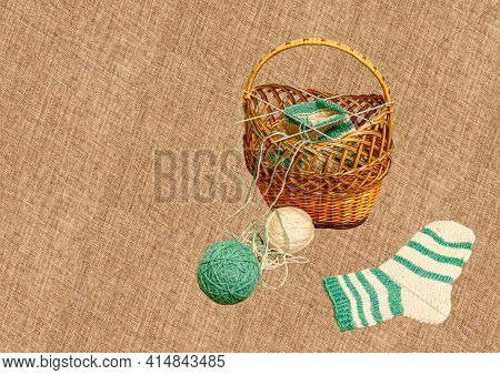 A Brown Wicker Basket With Started Knitting, White And Green Balls Of Yarn And A Finished Sock Are L