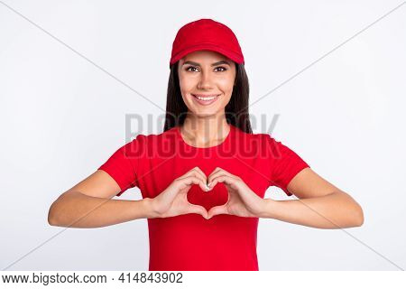 Photo Of Young Beautiful Smiling Cheerful Delivery Woman Showing Heart Gesture Isolated On Grey Colo
