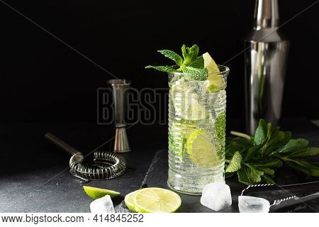 Refreshing Summer Mojito Cocktail With Ice Cubes, Fresh Mint And Lime On Black. Exotic Mojito Bevera