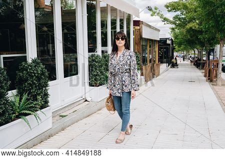 Lovely And Chic Woman Walking Along A Shopping Street On A Sunny Summer Day.