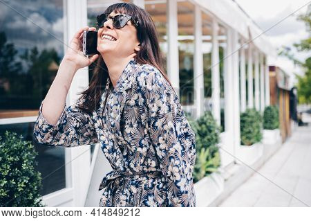 Elegant And Modern Happy Young Girl Talking Smiling On Her Mobile Phone In The Street.
