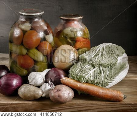 On A Shelf In The Basement Are Two Glass Jars Of Canned Tomatoes, Cucumbers And Peppers. Sealed With