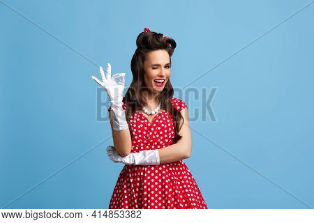 Beautiful Young Pin Up Woman In Polka Dot Red Dress And Gloves Showing Ok Gesture And Winking On Blu